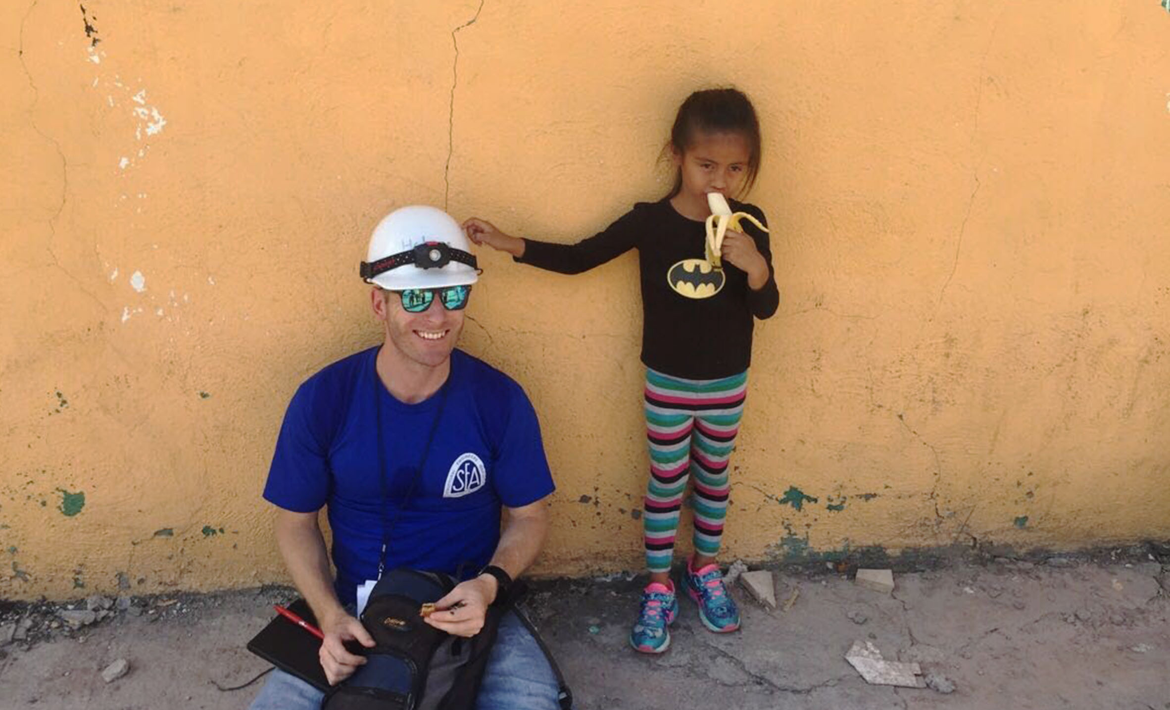 Dion Marriott of Holmes Structures rests in the shade with a young local girl who is wearing a batman shirt eating a banana