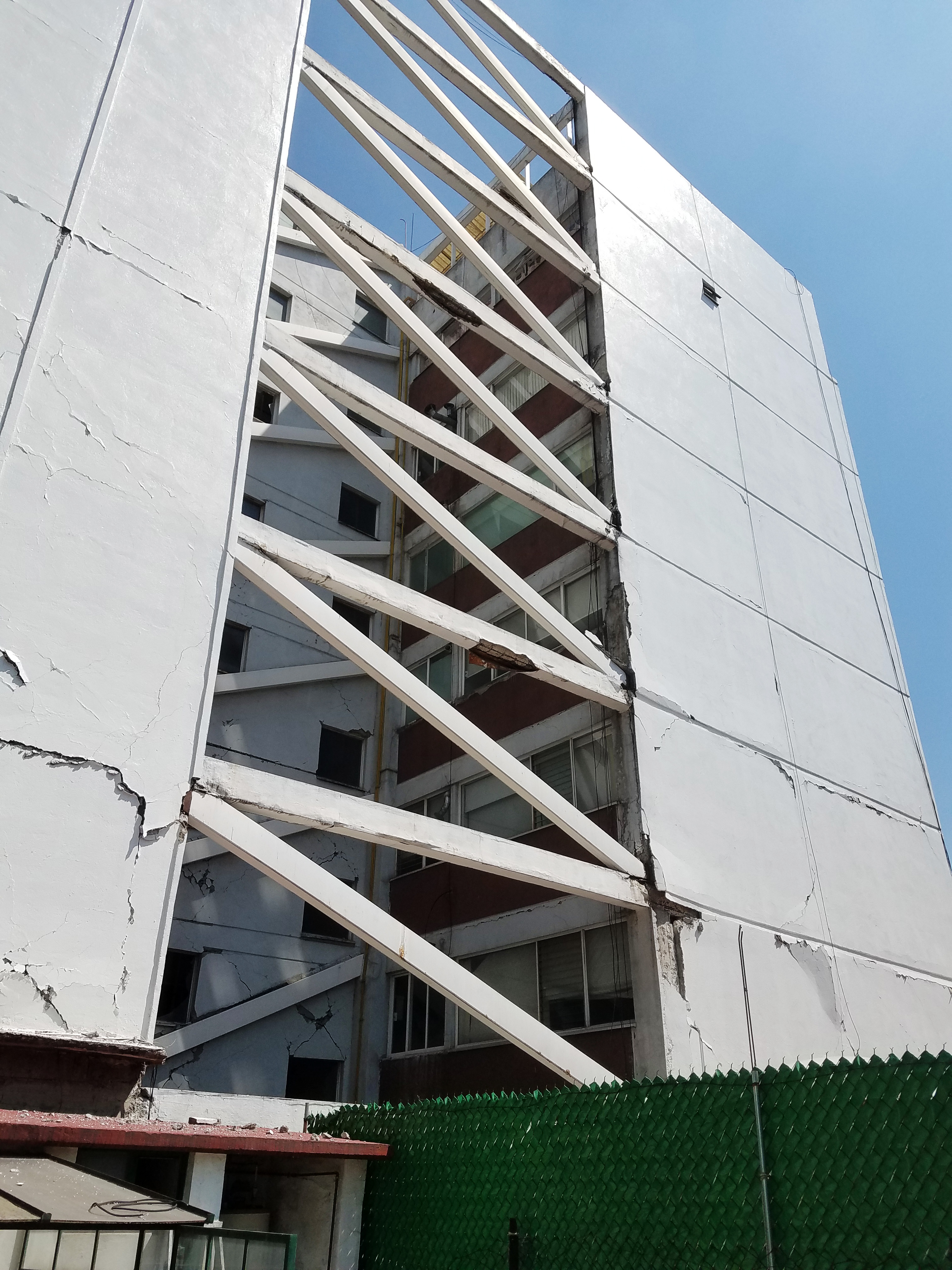 A damaged, retrofitted 8-story building at 81 Calle Amsterdam Mexico City with a cracked facade